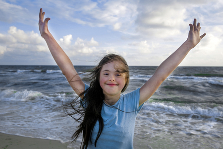 Portrait of down syndrome girl smiling on background of the sea Stock Photo
