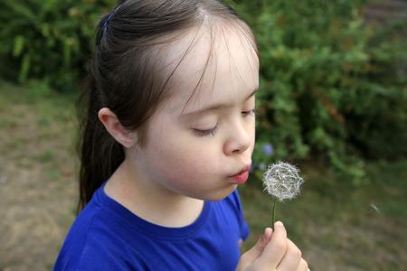 Little girl blowing dandelion Фото со стока