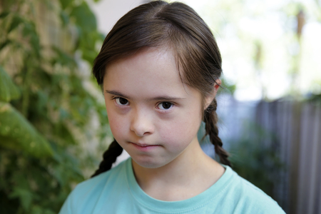 Portrait of down syndrome girl in the garden