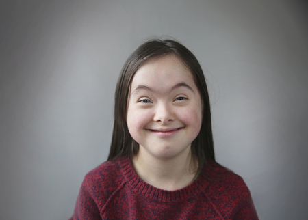 Cute smiling down syndrome girl on the grey background Stock Photo