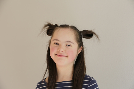 Cute smiling down syndrome girl on the grey background Foto de archivo