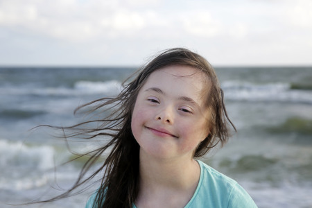 Portrait of down syndrome girl smiling on background of the sea Archivio Fotografico