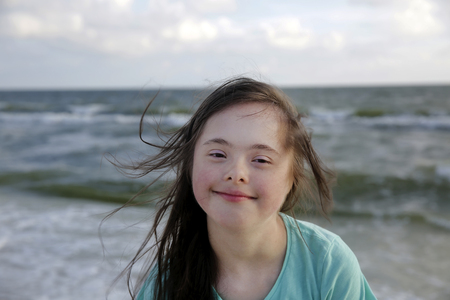 Portrait of down syndrome girl smiling on background of the sea Foto de archivo