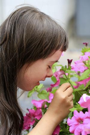 Little girl smells the flower