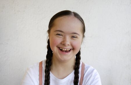 Portrait of little girl smiling on background of the wall