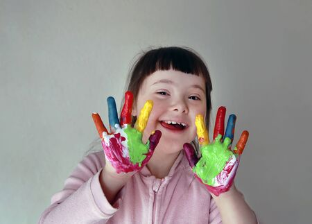 Cute little girl with painted hands. Isolated on grey background. 版權商用圖片