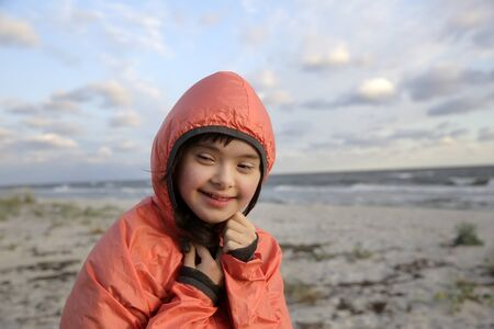 Portrait of down syndrome girl smiling on background of the sea 版權商用圖片