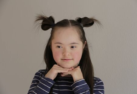 Cute smiling down syndrome girl on the grey