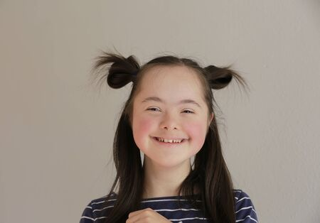 Cute smiling down syndrome girl on the grey background 版權商用圖片