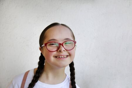 Portrait of little girl smiling on background of the wall 版權商用圖片