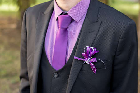 white boutonniere groom closeup. claret bow tie close-up