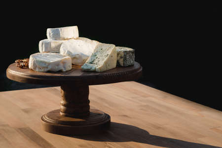 cheese plate. different cheeses on a wooden plate. Close up