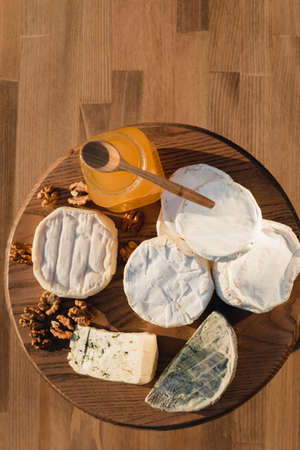 cheese plate. different cheeses on a wooden plate. cheeses of honey and nuts. Close up 写真素材