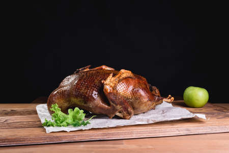 Roasted duck with apples. baked whole duck close-up on a platter on the table. Horizontal view from above