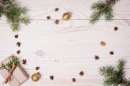 Christmas composition. Christmas gift, knitted blanket, pine cones, fir branches on wooden white background. Flat lay, top view, copy space 写真素材