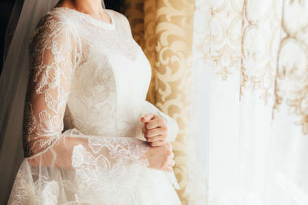 the bride in a beautiful dress is standing near the window. close up. copyspace. space for text 写真素材