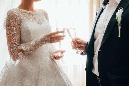beautiful wedding dress. beautiful newlyweds holding champagne glasses. close up