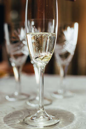 a glass of champagne and wedding rings. close up