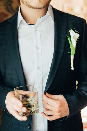groom holds a glass of whiskey. close up