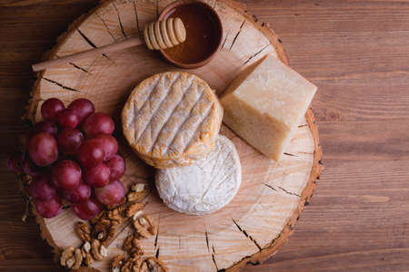 cheese plate on a wooden table. rustic. Close up. Space for text.