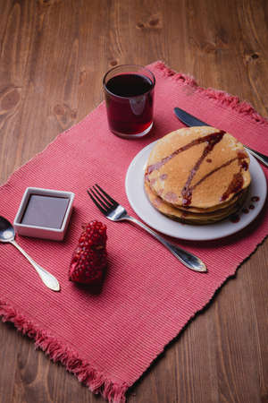 Pancakes with cherry syrup. Tea. Wooden table. Close up 写真素材