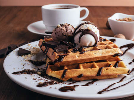 Belgian waffles with ice cream. Chocolate and nuts. wooden table. Rustik .Close up