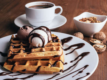 Belgian waffles with ice cream. Chocolate and nuts. wooden table. Rustic .Close up