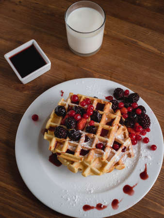 Belgian waffles with berries. milk. Syrup. Wooden table. Close up