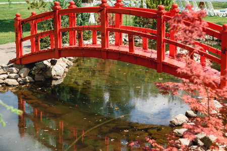 garden decor, red bridge. Chinese style. beautiful pond in the garden.
