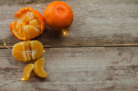 tangerines, peeled tangerine and tangerine slices on a white wooden table