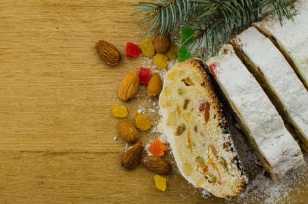 Christmas stollen on darkfestive background with fir twigs, lights and and berries. Close-up on this traditional German dessert for Christmas celebration.