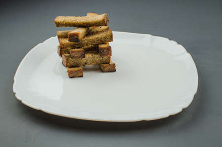 Toasts are fried on a frying pan with spices. Served on a white plate with garlic sauce