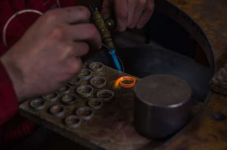 Craft jewelery making with professional tools. A handmade jeweler process, manufacture of jewellery. Melting metal