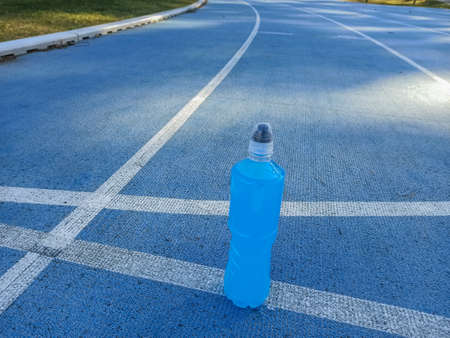 Isotonic energy drink. Bottle with blu transparent liquid, sport beverage on a sports ground. Start for running.