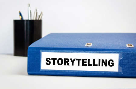Storytelling - the name of the folder is a registrar in blue on a table in an office with a pencil box.