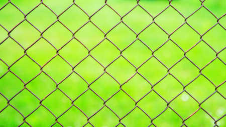 A wire mesh cage against a green meadow. Texture pattern surface background from wire mesh netting. Out of focus, defocus.