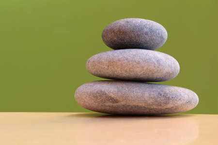 Three stones on a green background - harmony, stability, simplicity, peace Stock Photo