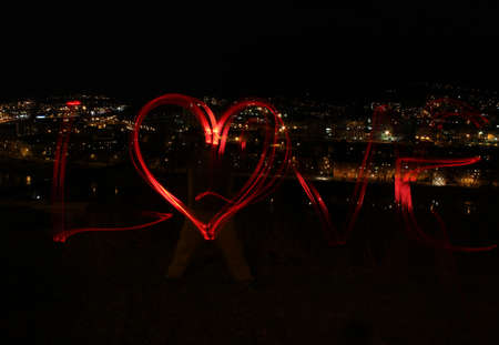 Blur photo made with red bike lamps  Sign love with heart before city