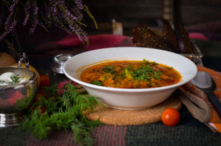 vegetable soup: Traditional ukrainian vegetable soup with sour cream and rye bread. National cuisine. Borscht. Soup with tomato, carrot, onion and potato. Rustic food background
