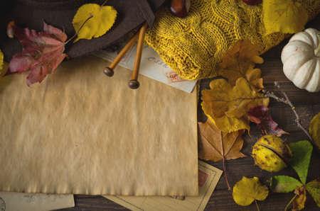 naranja arbol: Marco del otoño de la vendimia con las hojas amarillas, castañas, sombrero, cámara, agujas de tejer y sobres retro en el fondo de madera rústica. Punto de vista superior.