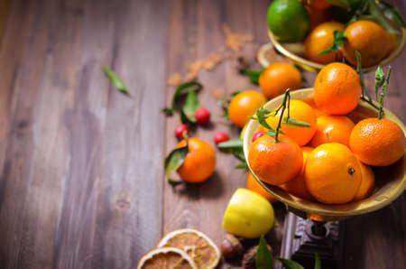 Dekorative Zusammensetzung der Weinlese mit Tangerinen, Zitrone in den alten Retro- Skalen, gezierte Kegel auf einem rustikalen hölzernen Hintergrund, Feiertagsdekoration, selektiver Fokus