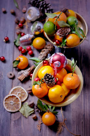 Cristmas: Vintage decorative Christmas fruits tangerines in old retro scales, spruce cones on a rustic wooden background, holiday decoration, Selective focus
