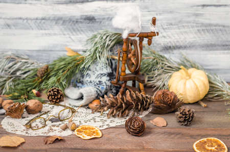 spinning wheel: New year and Christmas winter decoration on rustic wooden background with fir branches, cones, lace, antique glasses, vintage spinning wheel, pumpkin, orange slices and walnuts. Selective focus