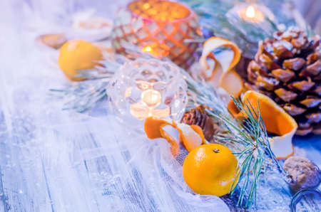 kinfolk: New year and Christmas winter decoration on rustic white wooden background with snow covered fir branches, tangerines, cones, candlestick, candle and orange slices. Top view, Copyspace background