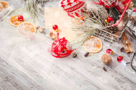 kinfolk: New year and Christmas winter decoration on rustic white wooden background with snow covered fir branches, tangerines, cones and shopping cart full of gifts. Copy space background