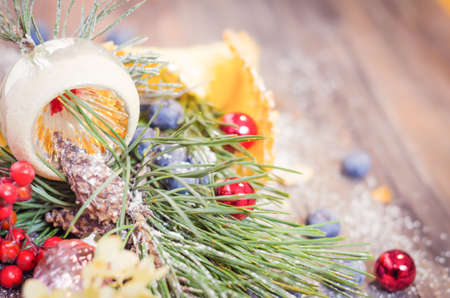 kinfolk: Festive scene with fir branches, blueberries, Christmas balls in a powdered waffle cone on rustic wooden background, Copy space, vintage decoration Stock Photo