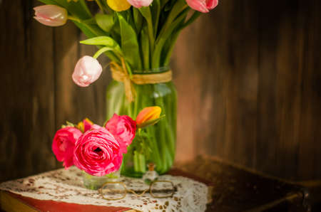 Vintage bunch of soft red flowers Ranunculus and tulips in a jar. Horizontal studio shot.