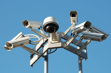 cctv: Security cameras mounting on the high top position against a clear blue sky