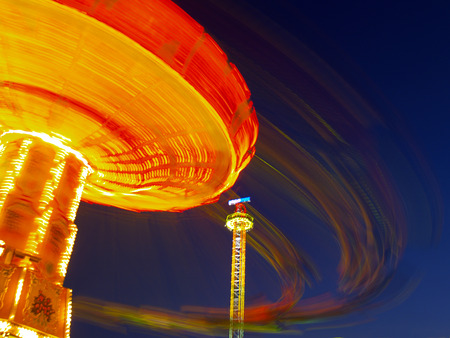 Chairloplane at the carnival, evening, motion blur Stock Photo