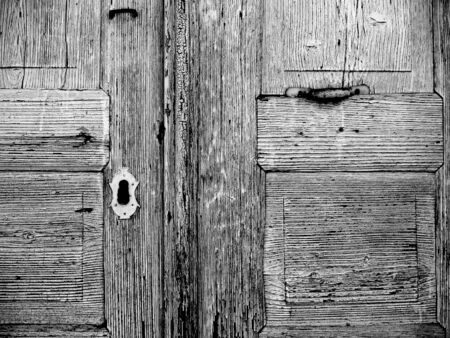 detail of an old weathered wooden door, keyhole, black white